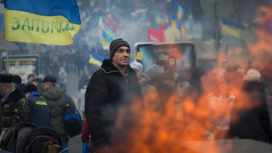 A Ukrainian pro-European Union activist stands while warming himself near a bonfire at a heavily fortified tent camp in the Independence Square in Kiev in Kiev, Ukraine, Tuesday, Dec. 17, 2013. Weeks of angry pro-European Union protests as well as Western pressure have forced Yanukoyvch to make some concessions to the opposition. Last week Yanukovych called for an amnesty for some of the activists detained. (AP Photo/Alexander Zemlianichenko)