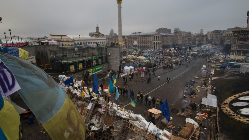 Pro-European Union activists stand guard at a barricades in front of a heavily fortified tent camp in Independence Square, Kiev, Ukraine, Tuesday, Dec. 17, 2013. Weeks of angry pro-European Union protests as well as Western pressure have forced Yanukoyvch to make some concessions to the opposition. Last week Yanukovych called for an amnesty for some of the activists detained. (AP Photo/Alexander Zemlianichenko)