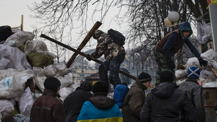 Pro-European Union activists reinforce the barricade to defense their tent camp at the Independence Square in Kiev, Ukraine, Tuesday, Dec. 17, 2013. Weeks of angry pro-European Union protests as well as Western pressure have forced President Viktor Yanukovych to make some concessions to the opposition. Russian President Vladimir Putin on Tuesday opened his wallet in the battle with the European Union over Ukraine's future, saying Moscow will buy $15 billion worth of Ukrainian government bonds and sharply cut the price of natural gas for its economically struggling neighbor. (AP Photo/Alexander Zemlianichenko)