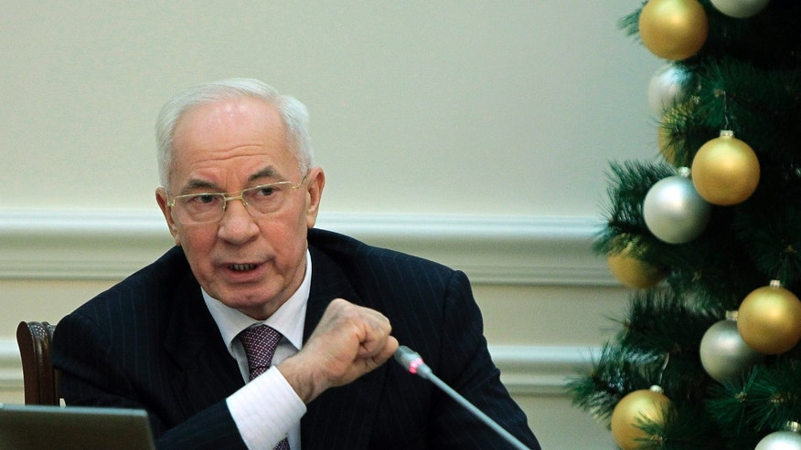 "Ukrainian Prime Minister Mykola Azarov speaks during a cabinet meeting in Kiev, Ukraine, Wednesday, Dec. 18, 2013. Since the mass anti-government protests started in Ukraine about a month ago, both the authorities and the opposition have been waging an information battle in a bid to intimidate, confuse and cajole their opponents, as well as the people of Ukraine. Putin and Yanukovych both pledged Tuesday, Dec. 17, 2013, to boost economic and trade ties to expand the ""strategic partnership"" between the two neighbors. (AP Photo/Sergei Chuzavkov)"