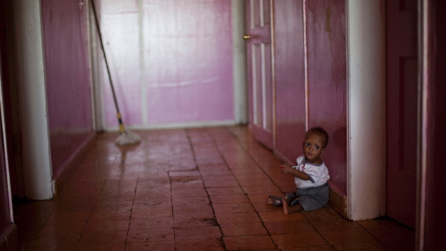 In this Nov. 13, 2013 photo. Ten month old Martelly Jean Louis, sits alone on the floor of the U.S.-based Church of Bible Understanding orphanage in Kenscoff, Haiti. The orphanage is run by a Christian missionary group funded by the Olde Good Things antique store on Manhattan's Upper West Side. While many other orphanages also have failed the Caribbean country's new national standards, and conditions are far worse in some, the group's three-story building on the hilly outskirts of Port-au-Prince stands out because it's run by an organization with such an unusual, and successful fundraising operation. The failure to meet the standards would seem to contradict their financial position.(AP Photo/Dieu Nalio Chery)