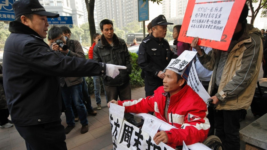 FILE - In this Thursday, Jan. 10, 2013 file photo, a policeman points at a supporter of Southern Weekly newspaper in a wheelchair before taken him away during a protest near the headquarters of the newspaper in Guangzhou, Guangdong province, China. Chinese authorities are ramping up prosecutions of rights activists during the year-end holidays, apparently hoping the West will pay less attention to its wide-ranging crackdown on dissent that has drawn international criticism throughout the year. Among the latest moves this week, Chinese prosecutors in the southern city indicted activist Liu Yuandong for leading free-speech demonstrations outside the newspaper's office in January. (AP Photo/ Vincent Yu, File)