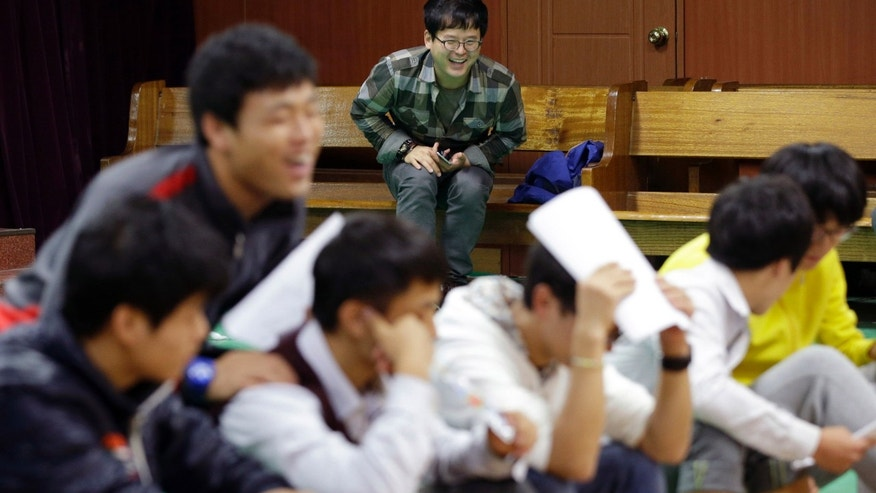 In this Oct. 29, 2013 photo, South Korea Kim Tae-hoon, center back, laughs as he watches practicing for a biannual public musical performed by his family in Seoul, South Korea. Kim is rearing nine boys - all defectors from North Korea. Kim has given them their first real experience of family. (AP Photo/Lee Jin-man)