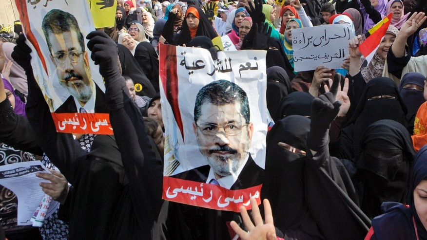 "FILE -- In this Nov. 1, 2013 file photo, supporters of Egypt's ousted President Mohammed Morsi hold his posters as they raise their hands with four fingers, which has become a symbol of the Rabaah al-Adawiya mosque, where Morsi supporters had held a sit-in for weeks that was violently dispersed in August, during a protest in Cairo, Egypt. Women supporters of the Muslim Brotherhood have stepped into the front line of Islamist protests against Egypt's military and the interim government installed after Morsi's removal in a July 3, 2013 coup. Arabic reads, ""yes to legitimacy,"" and ""Morsi is my president."" (AP Photo/Amr Nabil, File)"