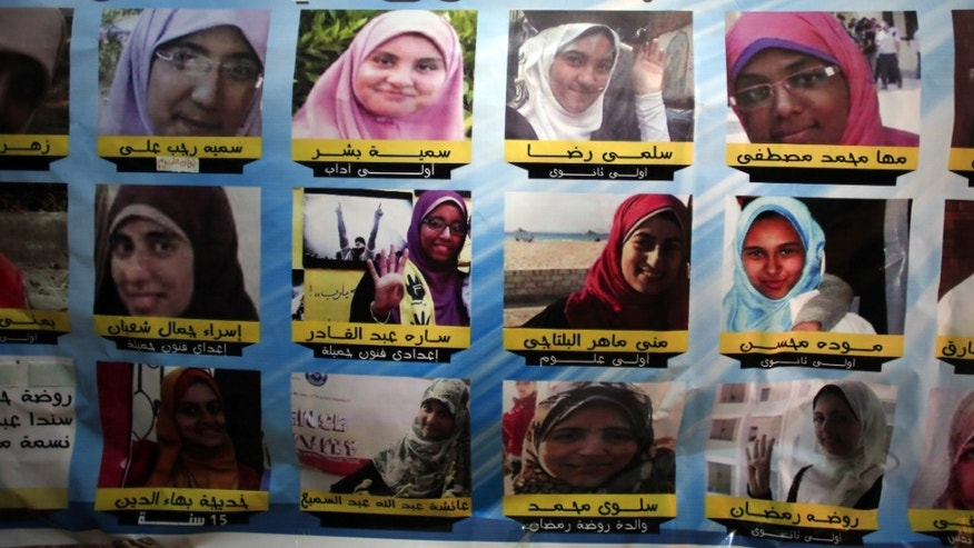 In this Thursday, Dec. 5, 2013 photo, a poster shows pictures and names of 17 girls who were arrested on Oct. 31, 2013, by Egyptian security during a protest by Muslim Brotherhood supporters, in the Mediterranean city of Alexandria, Egypt. Women supporters of the Muslim Brotherhood have stepped into the front line of Islamist protests against Egypt's military and the interim government installed after Morsi's removal in a July 3 coup. (AP Photo/Khalil Hamra)