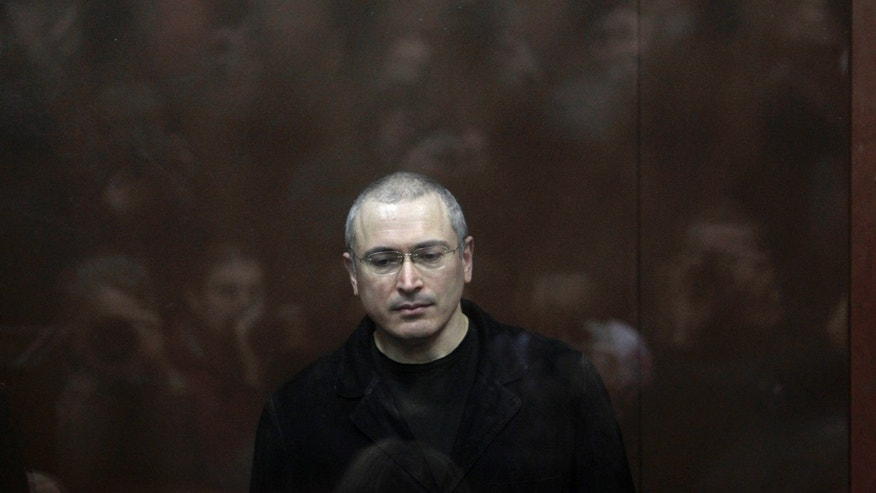 FILE - In this Monday, Dec. 27, 2010 file photo former oil tycoon Mikhail Khodorkovsky stands behind glass at a court room in Moscow, Russia. President Vladimir Putin says he will pardon jailed oil tycoon Mikhail Khodorkovsky after more than a decade in prison. Putin told reporters after his marathon news conference Thursday Dec. 19, 2013, that Khodorkovsky submitted an appeal for pardon and he intends to grant it. (AP Photo/Sergey Ponomarev, File)