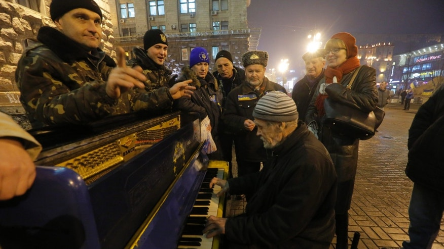 "A Pro-European Union activist plays a piano in a street towards a rally in Independence Square in Kiev, Ukraine, Wednesday, Dec. 18, 2013. Putin and Yanukovych both pledged Tuesday to boost economic and trade ties to expand the ""strategic partnership"" between the two neighbors. (AP Photo/Dmitry Lovetsky)"