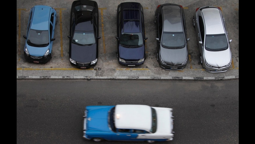 A vintage automobile drives by a parking lot of modern vehicles in Havana, Cuba, Thursday, Dec. 19, 2013. According to official media the government is opening the automobile market by eliminating the special permit that strictly limited the number of people allowed to buy vehicles from the state.  (AP Photo/Franklin Reyes)
