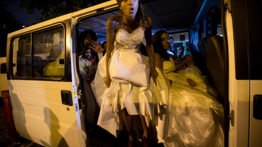 Mariana Reis, 15, stands in the doorway of a van in her debutante dress as she waits with fellow debutantes to attend a ball organized by the Pacifying Police Unit program, in Rio de Janeiro, Brazil, Thursday, Dec. 19, 2013. The debutante ball marks girls' transition from childhood to adulthood and is common in Brazil and other Latin American countries. The event relied on volunteers who coiffed and made up the girls and a formal wear shop that lent them the dresses. Girls were chosen on the strength of essays they wrote describing how life had changed since the pacifying police units, or UPPs set up shop in their communities.  (AP Photo/Silvia Izquierdo)