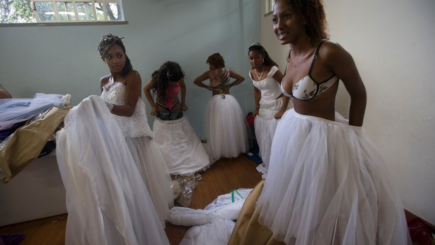 "Girls prepare for a debutante ball organized by the Pacifying Police Unit program, in Rio de Janeiro, Brazil, Thursday, Dec. 19, 2013. The young women who made their coming out Thursday night in a lavish Rio de Janeiro ceremony were not your typical society girls, but rather 15-year-olds from 36 of the city's ""favela"" slums, escorted by the police officers who patrol their communities. Girls were chosen on the strength of essays they wrote describing how life had changed since the UPPs set up shop in their communities.  (AP Photo/Silvia Izquierdo)"