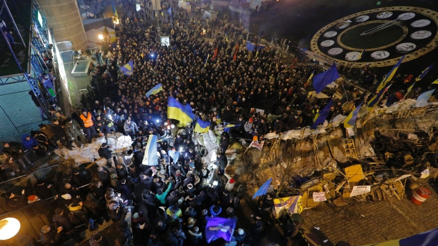 A crowd of pro-European Union activists, in back, block the entrance to Independence Square to supporters of Yanukovych's party of Regions in Kiev, Ukraine Thursday, Dec. 19, 2013. Thousands of anti-government demonstrators continued to occupy Kiev's Independence Square on Thursday, expressing their anger over a bailout Ukrainian President Viktor Yanukovych negotiated with Russia earlier this week. (AP Photo/Dmitry Lovetsky)