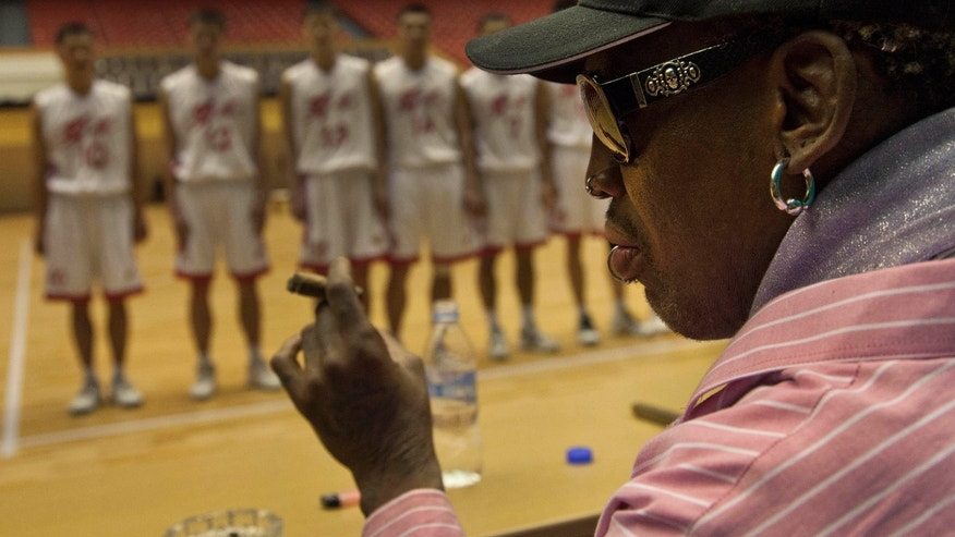 Former NBA basketball star Dennis Rodman holds a cigar as he speaks to North Korean basketball players during a practice session in Pyongyang, North Korea, Friday, Dec. 20, 2013. During the session, Rodman selected the members of the North Korean team who will play in Pyongyang against visiting NBA stars on Jan. 8, 2014, the birthday of North Korean leader Kim Jong Un. (AP Photo/David Guttenfelder)