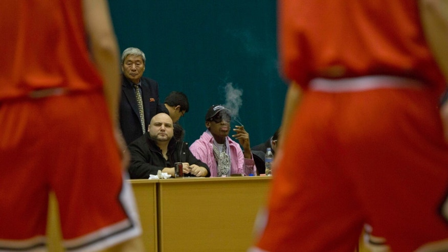 Former NBA basketball star Dennis Rodman smokes a cigar as he watches North Korean basketball players during a practice session in Pyongyang, North Korea on Friday, Dec. 20, 2013. Rodman selected the members of the North Korean team who will play in Pyongyang against visiting NBA stars on Jan. 8, 2014, the birthday of North Korean leader Kim Jong Un. (AP Photo/David Guttenfelder)