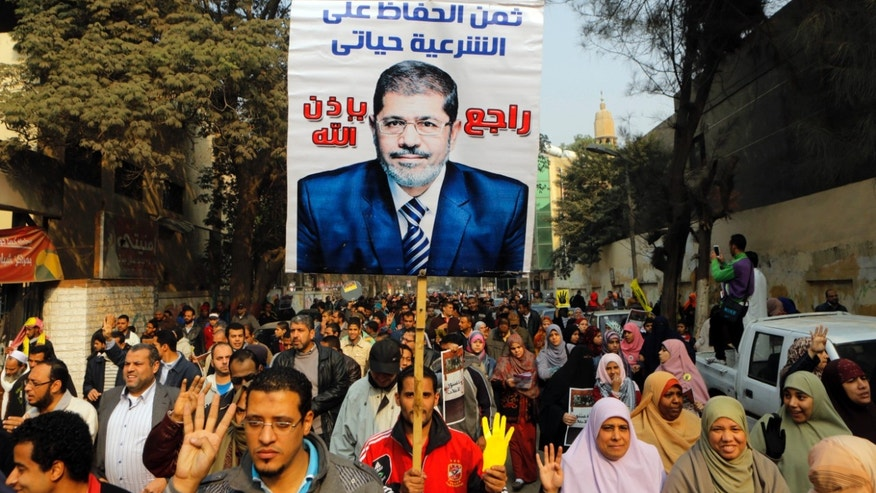 "Supporters of Egypt's ousted President Mohammed Morsi hold his poster as they raise their hands with four fingers which has become a symbol of the Rabaah al-Adawiya mosque, where Morsi supporters had held a sit-in for weeks that was violently dispersed in August, during a protest in Cairo, Egypt, Friday, Dec. 20, 2013. Arabic reads, "" my life is the cost to defend legitimacy, and Morsi will be back. (AP Photo/Amr Nabil)"