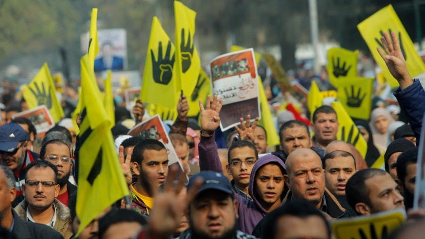 Supporters of Egypt's ousted President Mohammed Morsi raise flags with a logo showing a hand with four raised fingers which has become a symbol of the Rabaah al-Adawiya mosque, where Morsi supporters had held a sit-in for weeks that was violently dispersed in August, during a protest in Cairo, Egypt, Friday, Dec. 20, 2013. (AP Photo/Amr Nabil)