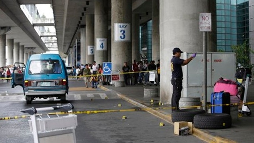 Dec. 20, 2013: Police investigators examine the bloodstained pavement at the Terminal 3 of the Ninoy Aquino International Airport following an ambush of a southern Philippine town mayor at suburban Pasay city south of Manila, Philippines.