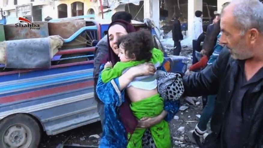 In this image taken from video obtained from the Shaam News Network, which has been authenticated based on its contents and other AP reporting, a woman carries a child out of a building after a blast at the building in Aleppo, Syria, Thursday, Dec. 19, 2013. In northern Syria, government war planes have bombed rebel-held districts of Aleppo for the fifth straight day, leveling apartment buildings, flooding hospitals with casualties in attacks that have so far killed nearly 200 people, activists said. (AP Photo/Shaam News Network via AP Video)