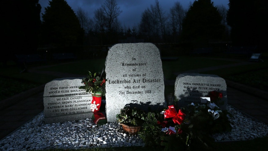 Floral tributes are seen near the main memorial stone in memory of the victims of Pan Am flight 103 bombing in the garden of remembrance at Dryfesdale Cemetery, near Lockerbie, Scotland, Saturday, Dec. 21, 2013. Pan Am flight 103 was blown apart above the Scottish border town of Lockerbie on Dec. 21, 1988. All 269 passengers and crew on the flight and 11 people on the ground were killed in the bombing. (AP Photo/Scott Heppell).