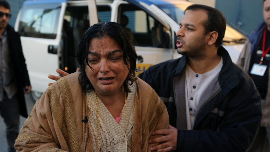 Fatima Khan, left, mother of the deceased British doctor Abbas Khan, 32, who was seized by Syrian government troops in November 2012, cries while her son Afroze Khan consoles her as they enter the Hotel-Dieu de France hospital in Beirut, Lebanon, Saturday, Dec. 21, 2013. The circumstances in which Khan died while in detention in Syria remain in dispute. A senior British official has accused Syrian President Bashar Assad's government of effectively murdering Khan, while the Syrian authorities say the doctor committed suicide and there was no sign of violence or abuse. (AP Photo/Bilal Hussein)