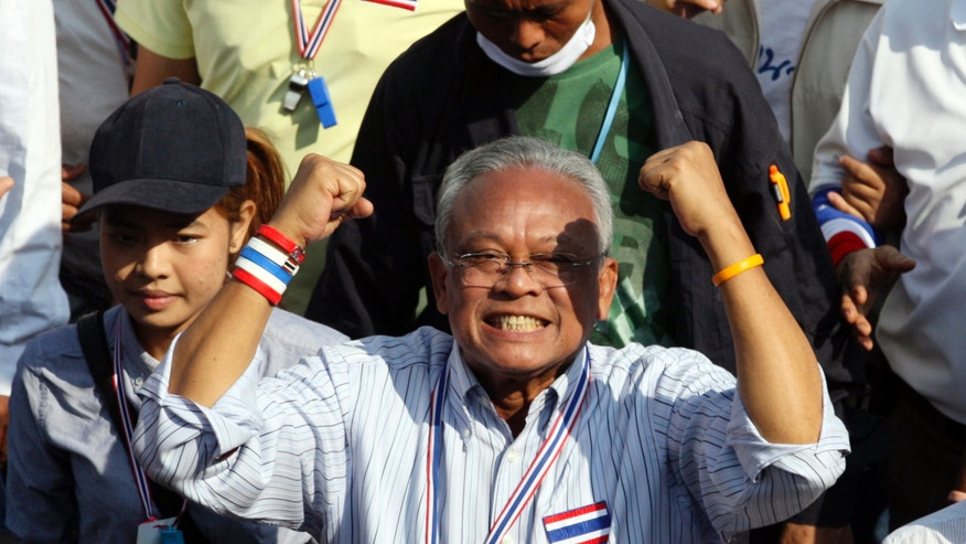 Thai anti-government protest leader Suthep Thaugsuban holds clenched fists during a march with his supporters in Bangkok, Thailand Sunday, Dec. 22, 2013. Thailand's main opposition Democrat Party said it would boycott February's general election, deepening a political crisis as protesters called for another major rally Sunday to step up efforts to oust the government and force political reforms. (AP Photo/Sakchai Lalit)
