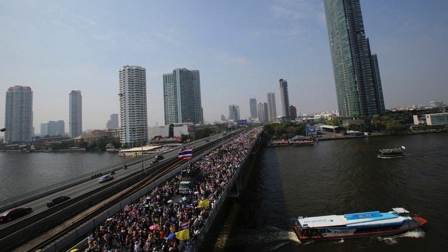 Thai anti-government protesters march cross Takin Bridge during a rally  Sunday, Dec. 22, 2013, in Bangkok, Thailand. Thailand's main opposition Democrat Party said it would boycott February's general election, deepening a political crisis as protesters called for another major rally Sunday to step up efforts to oust the government and force political reforms.(AP Photo/Sakchai Lalit)