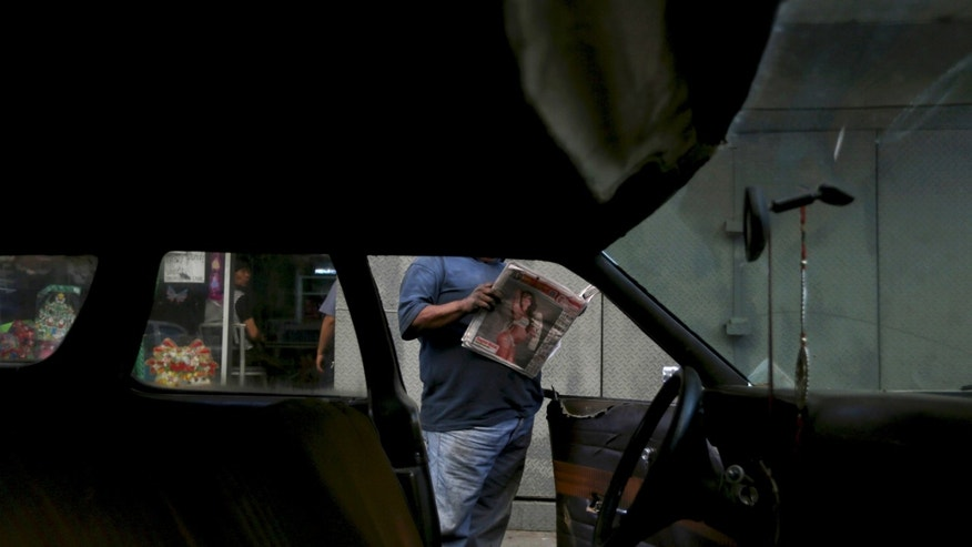 In this Thursday, Dec. 19, 2013 photo, Ruben Ruiz reads a newspaper next to his 1975 Ford LTD station wagon at a taxi stand in Caracas, Venezuela. But all good things must come to an end. For Venezuelan motorists, to whom cheap gas is something of a birthright and fuel efficiency a foreign concept, that means having to pay more at the pump. But Ruiz has held onto the rusting hulk though subsequent oil booms and busts, its velvet upholstery ripped apart and passenger doors impossible to open from the inside. He said modern cars don't afford the same heft or trunk space. And having paid off the initial investment several times over, the last thing he's worried about is a fuel hike. (AP Photo/Fernando Llano)