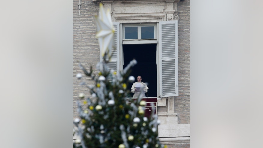 Pope Francis, framed by a Christmas tree, delivers his message to faithful gathered in St. Peter's Square during the Angelus prayer, at the Vatican, Sunday, Dec. 22, 2013. (AP Photo/Gregorio Borgia)