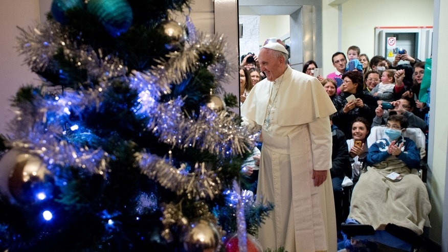 In this picture provided by the Vatican newspaper L'Osservatore Romano, Pope Francis is framed by a Christmas tree as he visits a ward at the Bambino Gesu' pediatric hospital, in Rome, Saturday, Dec. 21, 2013. Francis spent three hours visiting patients and their families and is the fifth pontiff to visit the hospital, which is controlled by the Vatican's secretary of state. (AP Photo/L'Osservatore Romano, ho)