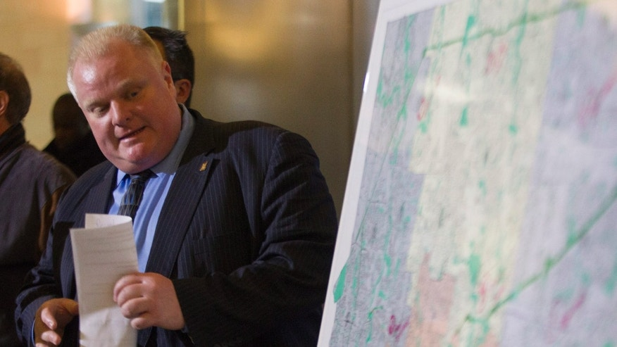 Toronto Mayor Rob Ford refers to a map of the city at a news conference to address an ice storm that left over 250,000 customers across the city without power on Sunday, Dec. 22, 2013. (AP Photo/The Canadian Press, Chris Young)