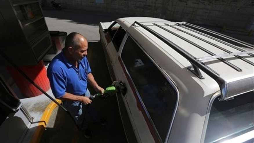 Henry Duran fills the tank of his 1978 Ford LTD Ranger at a gas station in Caracas, Venezuela, Saturday, Dec. 21, 2013. The loud, steady roar of Nixon-era gas guzzlers is sounding a little less muscular these days on the smog-filled streets of Caracas. As a grueling economic crisis drains the governments coffers, President Nicolas Maduro is putting motorists on notice and taking on one of the nations biggest political taboos: the low price of gas. (AP Photo/Fernando Llano)