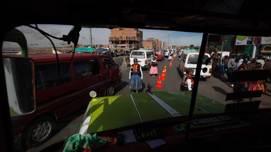 "In this Dec. 3, 2013 photo, Aymara women traffic cops, seen through the windshield of a bus, direct traffic on the streets of El Alto, Bolivia. About 20 so-called ""traffic cholitas"" have been trained to direct cars and buses in El Alto, the teeming, impoverished sister city of La Paz in the Bolivia's Andes mountains. (AP Photo/Juan Karita)"