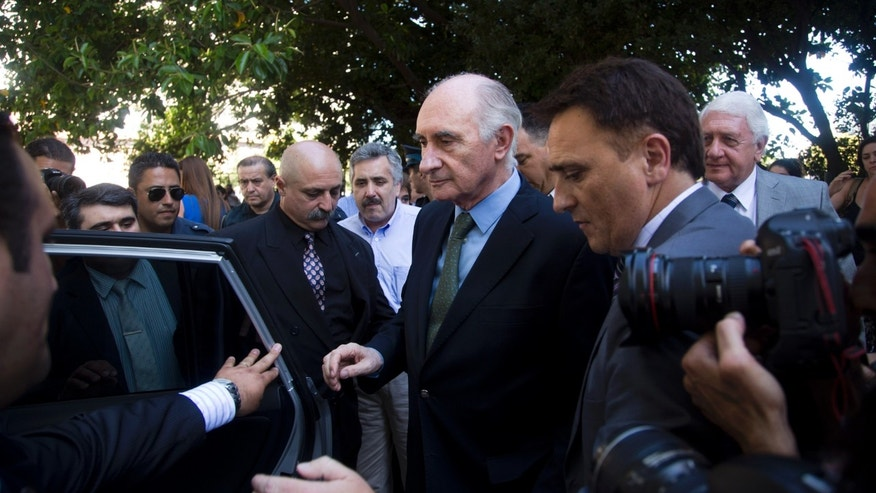 Former Argentine President Fernando de la Rua walks into a car outside Argentina's Federal Court in Buenos Aires, Argentina, Monday, Dec. 23, 2013. De la Rua was found innocent of bribing senators to pass a law weakening worker protections as the country's economy neared collapse 13 years ago. (AP Photo/Victor R. Caivano)
