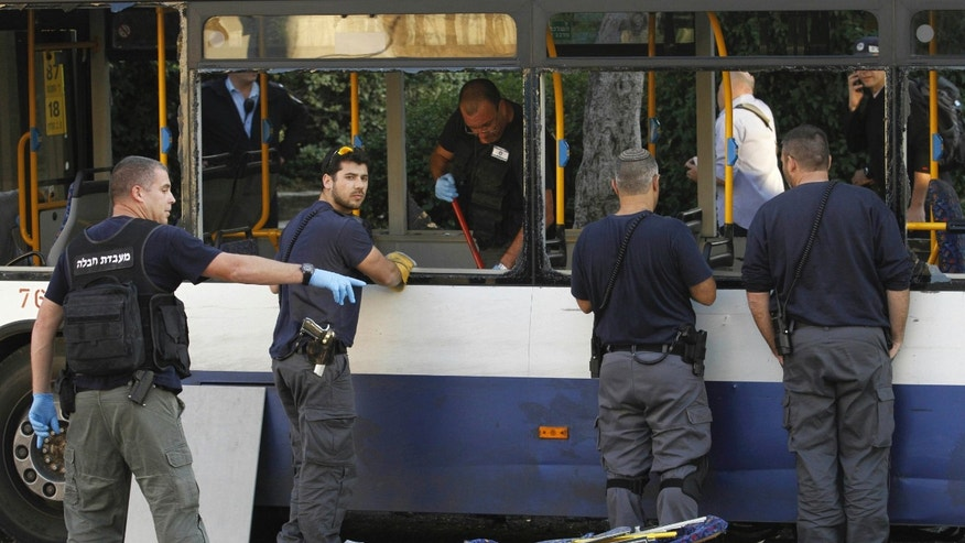 Israeli policemen inspect a bus after an explosive device detonated in a Tel Aviv suburb, Sunday, Dec. 22, 2013. A small bomb exploded on board the bus just moments after it had been evacuated on Sunday, police said, adding that an initial investigation suggests that Palestinian militants were behind the attack. (AP Photo/Tomer Appelboum) ISRAEL OUT