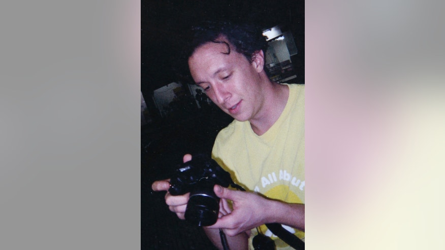 FILE  - This undated file photo released by the Martin family shows American Joseph Martin handling a camera in an unknown location. In May of 2007, Martin was shot and killed by an off-duty police officer following an altercation with police over a stolen purse while out celebrating his 30th birthday in Rio de Janeiro, Brazil. Martin had been living in Brazil for about two years and supported himself by teaching English. (AP Photo/Martin family, File)