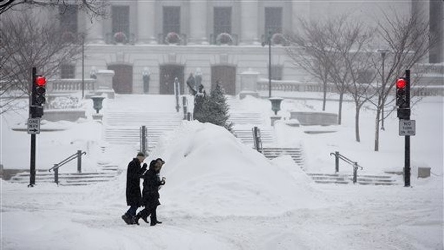 Pedestrians cross State Street on the Capitol Square after a snowfall in Madison, Wis., Sunday, Dec. 22, 2013. (AP Photo/Wisconsin State Journal, Steve Apps)