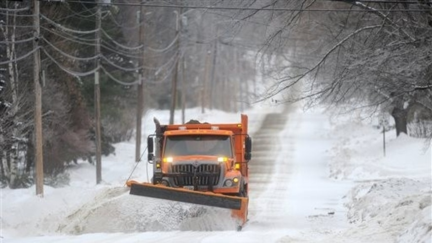 A Waterville Public Works snowplow clears Mayflower Hill Drive as a major ice storm rolls through Waterville, Maine, on Sunday morning, Dec. 22, 2013. (AP Photo/The Central Maine Morning Sentinel, Michael G. Seamans)