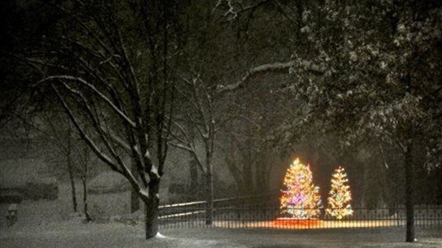 This Dec. 21, 2013 photo shows Christmas tree lights illuminating a yard as the snow falls late Saturday night Dec. 21, 2013, in Salina, Kan. A snow storm dropped almost a foot of snow Saturday night and Sunday morning in the Salina area. (AP Photo/Salina Journal, Tom Dorsey)