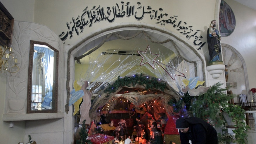 "Palestinian Christian nun Rosaria, prepares a Nativity scene at the Latin Patriarch of Jerusalem Church of Visitation, also known as St. Mary's Visitation Church, in preparation for Christmas in the northern West Bank village of Zababdeh near Jenin, Tuesday, Dec. 24, 2013. Arabic writing from the Bible, Mathew 18:3, reads, ""Unless you are converted and become as little children, you will by no means enter the Kingdom of Heaven."" (AP Photo/Mohammed Ballas)"