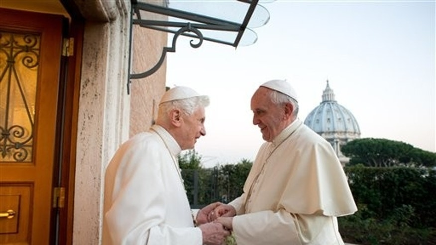 Pope Emeritus Benedict XVI welcomes Pope Francis at the Vatican, Monday, Dec. 23, 2013.