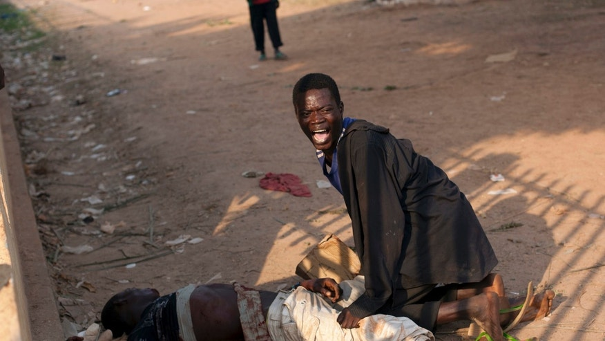 A young man reacts after his friend was badly injured by passing Chadian troops, during a protest outside Mpoko Airport in Bangui, Central African Republic, Monday, Dec. 23, 2013. Hundreds of demonstrators gathered at the entrance to the airport Monday morning carrying signs protesting Chadian forces and expressing support for French troops and other regional African forces. At least two people were wounded as pickups of Chadian soldiers sped through the gathered crowd firing off several rounds. (AP Photo/Rebecca Blackwell)