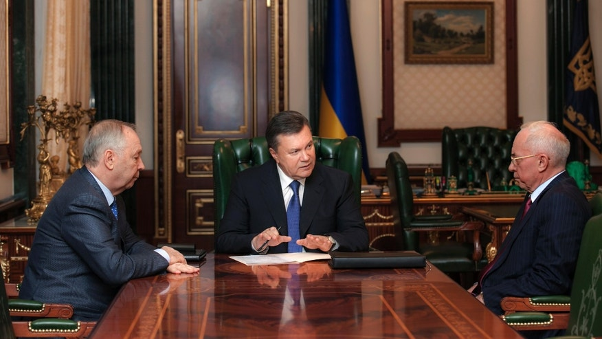 Ukrainian President Viktor Yanukovych, center, speaks during a meeting with Ukrainian Prime Minister Mykola Azarov, right, and Ukrainian parliament speaker Volodymyr Rybak, left, in Kiev, Ukraine, Monday, Dec. 23, 2013.  (AP Photo/ Andrei Mosienko, Pool)