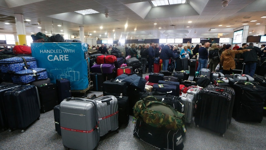 Luggage belonging to passengers piles up following a power outage at the North Terminal of London Gatwick Airport in Horley, England, Tuesday, Dec. 24, 2013. A severe winter storm has caused major travel problems in Britain, leading to substantial delays Tuesday at London Gatwick Airport and on roads and rail lines at the height of the Christmas travel period. (AP Photo/Sang Tan)