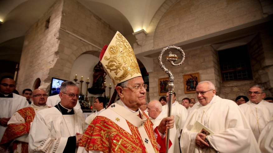 Latin Patriarch of Jerusalem, Fouad Twal, leads the midnight Christmas mass at the Church of Nativity, traditionally believed by Christians to be the birthplace of Jesus Christ, in the West Bank town of Bethlehem on Christmas Eve, Wednesday, Dec. 25, 2013. (AP Photo/Musa Al-Shaer, Pool)