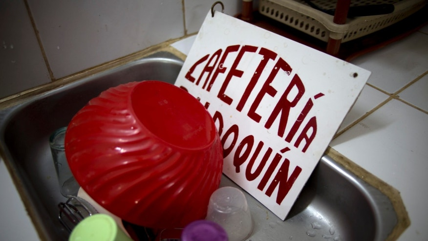 "In this Dec. 24, 2013 photo, a business sign for ""Cafeteria Baldoquin"" run by Julio Cesar Hidalgo sits in the sink of his home where he ran his pizza joint in Havana, Cuba. Two years on the front lines of Cuba's experiment with limited free market capitalism has left Hidalgo broke, out of work and facing a possible crushing fine. Hidalgo says he has not given up on the idea of opening a new business one day. But he is also setting his sights beyond Cuba's shores. (AP Photo/Ramon Espinosa)"
