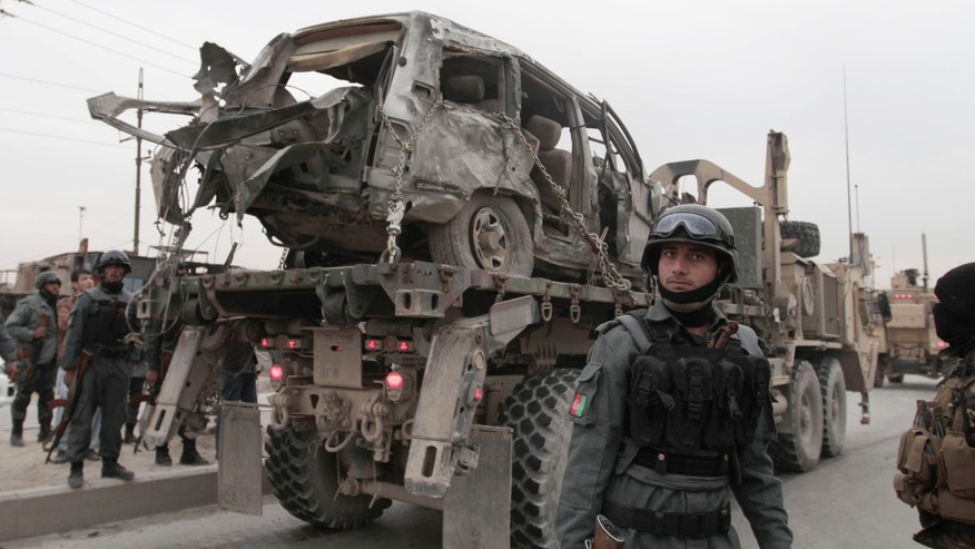 Dec. 27, 2013 - A U.S. military wrecker carries away a vehicle destroyed in a suicide car bomb attack on the Jalalabad-Kabul road in Kabul, Afghanistan. The U.S.-led coalition in Afghanistan says several service members were killed Friday when a suicide car bomber attacked their convoy in an eastern district of the capital, Kabul.