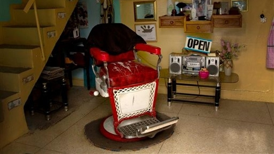 A chair sits empty in the home of Maleidy Blanco who runs a barbershop here in Havana, Cuba, Thursday, Dec. 26, 2013. After a surge of enthusiasm, the number of islanders working for themselves has stalled for the past two years at less than 10 percent of the workforce. (AP Photo/Ramon Espinosa)