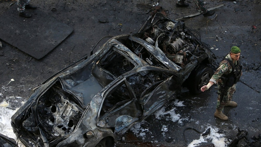A Lebanese Army soldier stands next to a destroyed car at the scene of an explosion in central Beirut, Lebanon, Friday, Dec. 27, 2013. The state news agency said a bombing in central Beirut has killed several people, including Mohammed Chatah, a senior aide to former Lebanese Prime Minister Saad Hariri. (AP Photo/Hussein Malla)