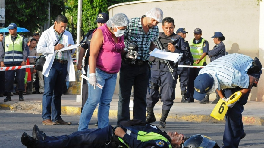 "ADVANCE FOR SATURDAY, DEC. 28AND THEREAFTER - EDS NOTE GRAPHIC CONTENT - FILE - This Aug. 7, 2013 file photo shows investigators standing over the body of traffic policeman Santos Arita, after he was allegedly killed by two young gang members in Tegucigalpa, Honduras. With the highest murder rate in the world, Honduras is a dangerous country. Its capital is a city where people watch murders on YouTube, wake up to photos of the dead in the newspapers and drive by their dumped bodies on the outskirts of town. It is a country where the disparaging concept of the ""banana republic"" was born, when U.S. fruit companies used the Honduran military to control labor, but it is not a nation that recovered from a legacy that favored the interests of the few over those of the many. (AP Photo/Fernando Antonio, File)"