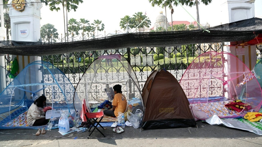 Thai anti-government protesters do their morning duty inside mosquito's nets at a makeshift camp where their colleagues were shot outside the prime minister's office of Government House, background, Saturday, Dec. 28, 2013 in Bangkok, Thailand. Gunmen killed an anti-government protester and wounded two others in the Thai capital on Saturday, raising fears that the country's deepening political crisis was headed toward sustained violence on the streets of Bangkok. (AP Photo/Apichart Weerawong)