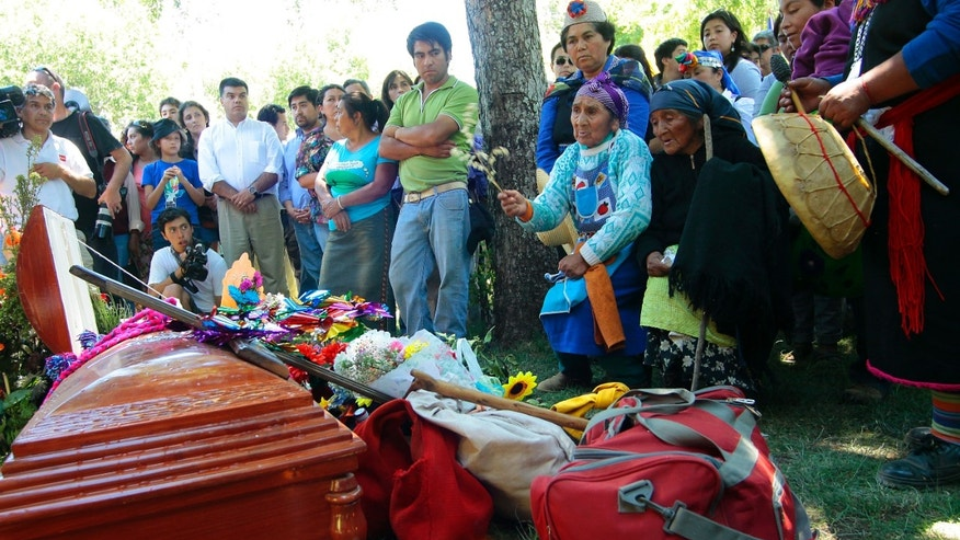 Berta Quintreman, holding a plant in her hand, kneels next to the casket of her sister Nicolasa, a Mapuche Indian leader, at her funeral in Ralco, Chile, Friday, Dec. 27, 2013. With her sister Berta, Quintreman became a national figure in Chile during protests against the construction of a hydroelectric dam on tribal land in the forested mountains of southern Chile. The 73-year-old Indian leader was found floating Tuesday in the reservoir she spent a decade trying to prevent from being created. (AP Photo/Victor Salazar, AgenciaUno)